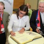 Raffaella Delli Santi trägt sich ins Goldene Buch der Stadt Kolbermoor ein, daneben Bürgermeister Peter Kloo (li.) und SV-DJK- Vorstandssprecher Gerhard Duschl